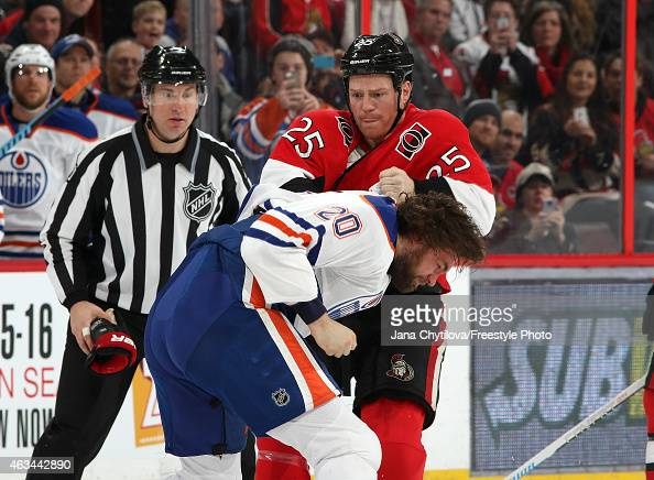 Chris Neil of the Ottawa Senators fights Luke Gazdic of the Edmonton Oilers in the second period at Canadian Tire Centre on February 14 2015 in...
