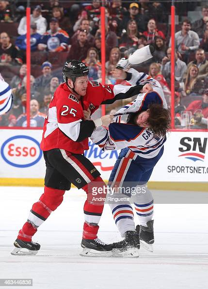Chris Neil of the Ottawa Senators fights with Luke Gazdic of the Edmonton Oilers during an NHL game at Canadian Tire Centre on February 14 2015 in...