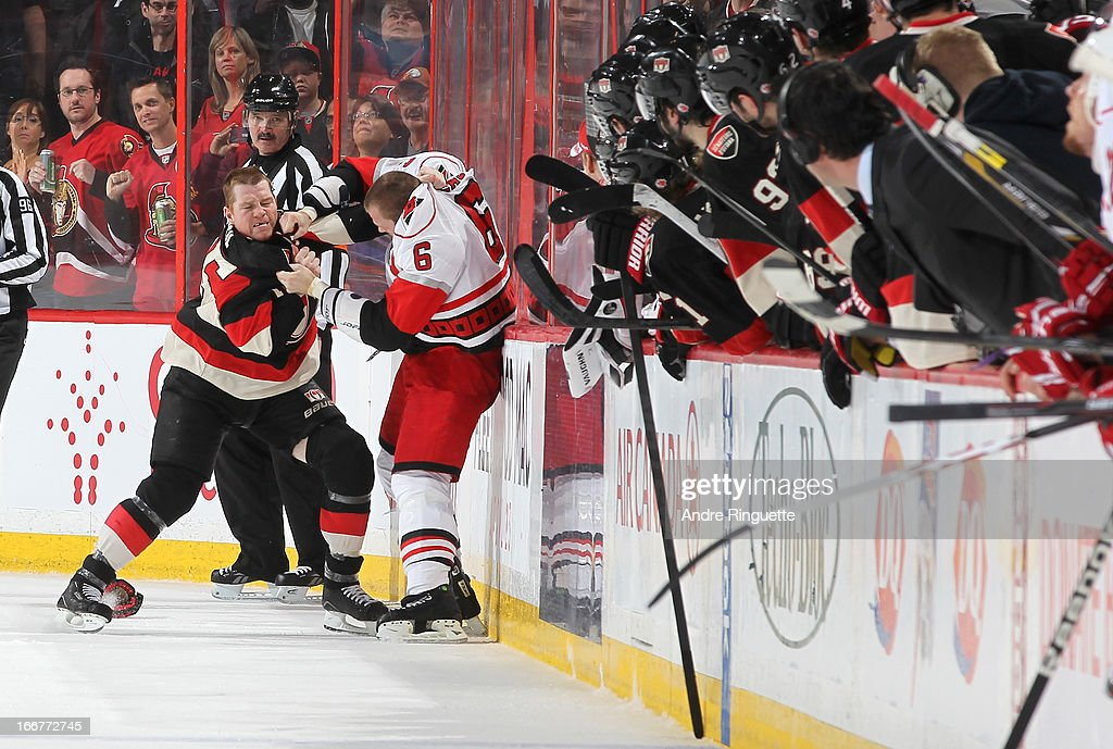 Chris Neil #25 of the Ottawa Senators fights with <a gi-track='captionPersonalityLinkClicked' href=/galleries/search?phrase=Tim+Gleason&family=editorial&specificpeople=211575 ng-click='$event.stopPropagation()'>Tim Gleason</a> #6 of the Carolina Hurricanes as players look on from the bench on April 16, 2013 at Scotiabank Place in Ottawa, Ontario, Canada.