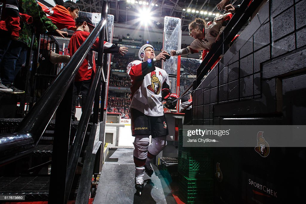 Chris Neil of the Ottawa Senators fist bumps a fan as he steps off the ice following the warmup skate prior to an NHL game against the Anaheim Ducks...