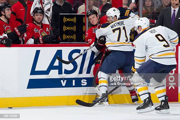 Chris Neil of the Ottawa Senators gets checked along the boards by Derek Whitmore of the Buffalo Sabres during an NHL game at Scotiabank Place on...