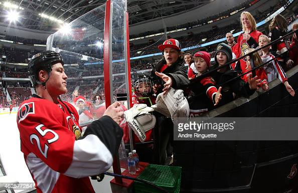 Chris Neil of the Ottawa Senators gives a souvenir puck to young fans after warmup prior to a game against the Arizona Coyotes at Canadian Tire...