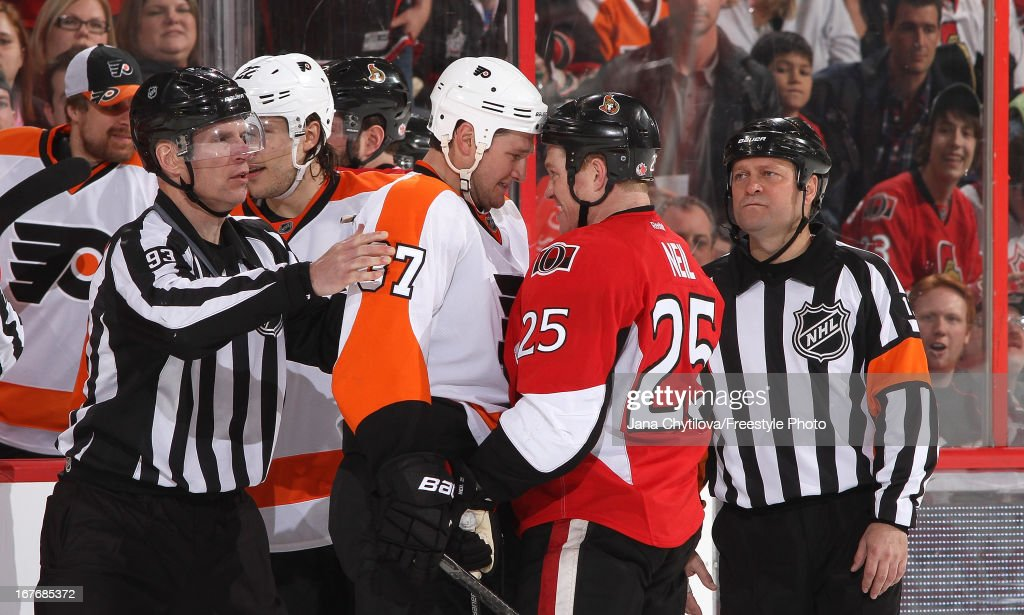 Chris Neil #25 of the Ottawa Senators glares at Jay Rosehill #37 of the Philadelphia Flyers as linesman Brian Murphy #93 and referee <a gi-track='captionPersonalityLinkClicked' href=/galleries/search?phrase=Dan+O%27Halloran&family=editorial&specificpeople=622039 ng-click='$event.stopPropagation()'>Dan O'Halloran</a> #13 keep an eye on the situation, during an NHL game, at Scotiabank Place, on April 27, 2013 in Ottawa, Ontario, Canada.