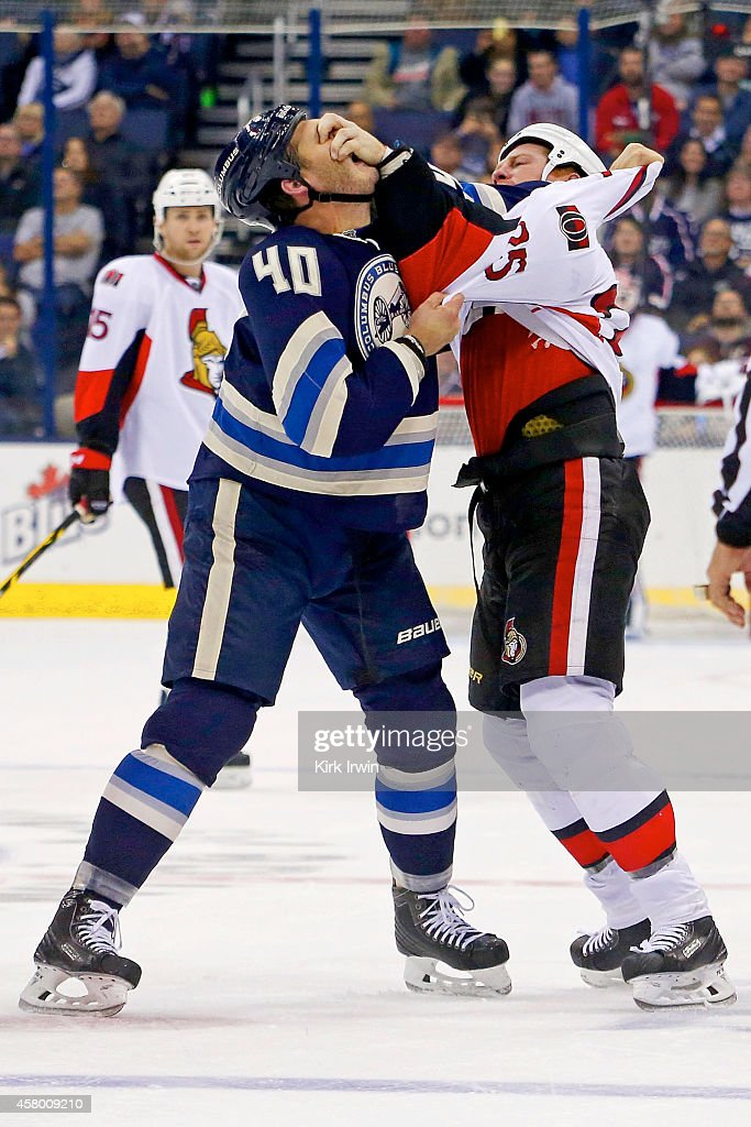 Chris Neil of the Ottawa Senators gouges the eyes of Jared Boll of the Columbus Blue Jackets during a fight in the first period on October 28 2014 at...
