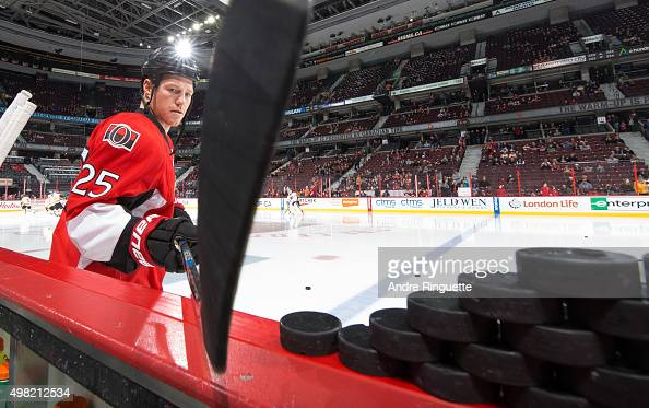 Chris Neil of the Ottawa Senators grabs the warmup pucks with his stick prior to a game against the Philadelphia Flyers at Canadian Tire Centre on...