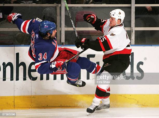 Chris Neil of the Ottawa Senators hits Jason Strudwick of the New York Rangers on April 18 2006 at Madison Square Garden in New York City The...