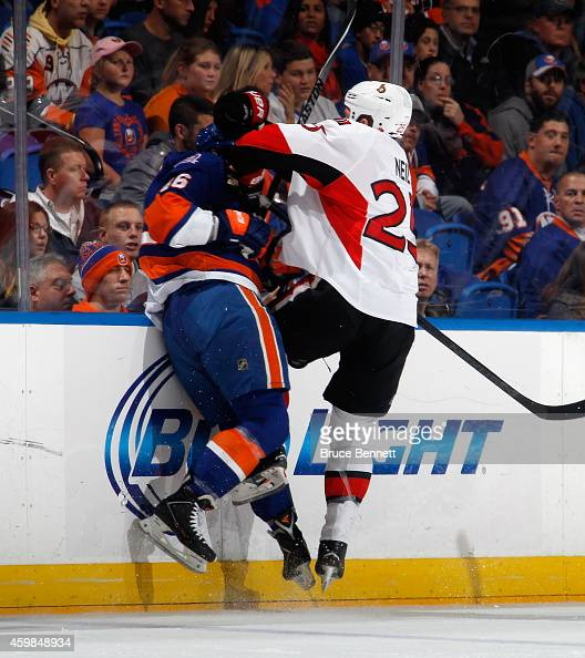 Chris Neil of the Ottawa Senators hits Matt Donovan of the New York Islanders into the boards during the first period at the Nassau Veterans Memorial...