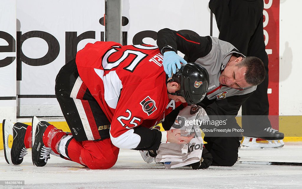 Chris Neil #25 of the Ottawa Senators is attended by Head Athletic Trainer Gerry Townend, after Neil sustained a facial cut from a high stick, during an NHL game against the Boston Bruins, at Scotiabank Place, on March 21, 2013 in Ottawa, Ontario, Canada.