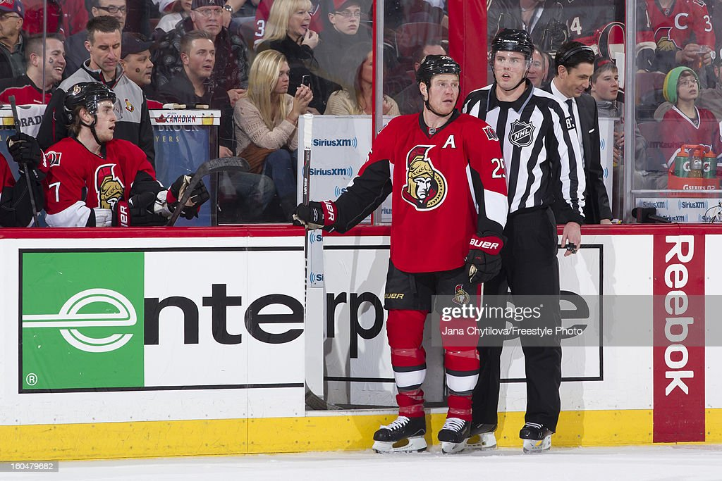 Chris Neil #25 of the Ottawa Senators is watched by linesman Matt MacPherson #83 after a penalty call during an NHL game against the Montreal Canadiens at Scotiabank Place on January 30, 2013 in Ottawa, Ontario, Canada.