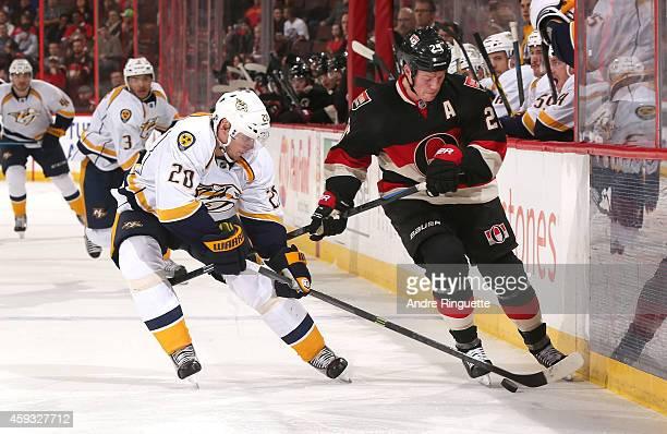 Chris Neil of the Ottawa Senators kicks the puck forward along the boards against pressure form Anton Volchenkov of the Nashville Predators at...