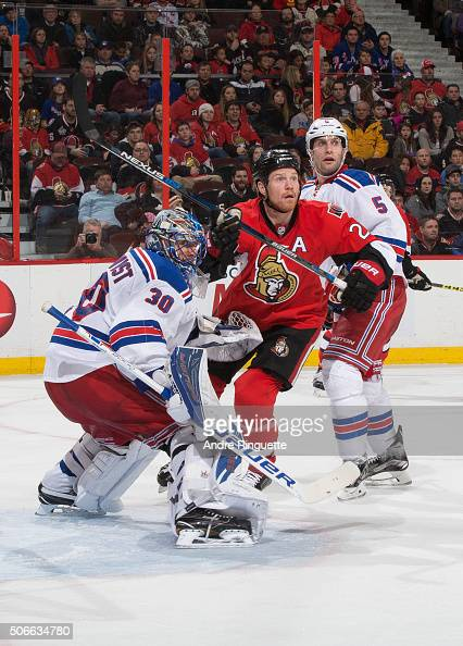 Chris Neil of the Ottawa Senators looks for the puck in the air with Henrik Lundqvist and Dan Girardi of the New York Rangers at Canadian Tire Centre...