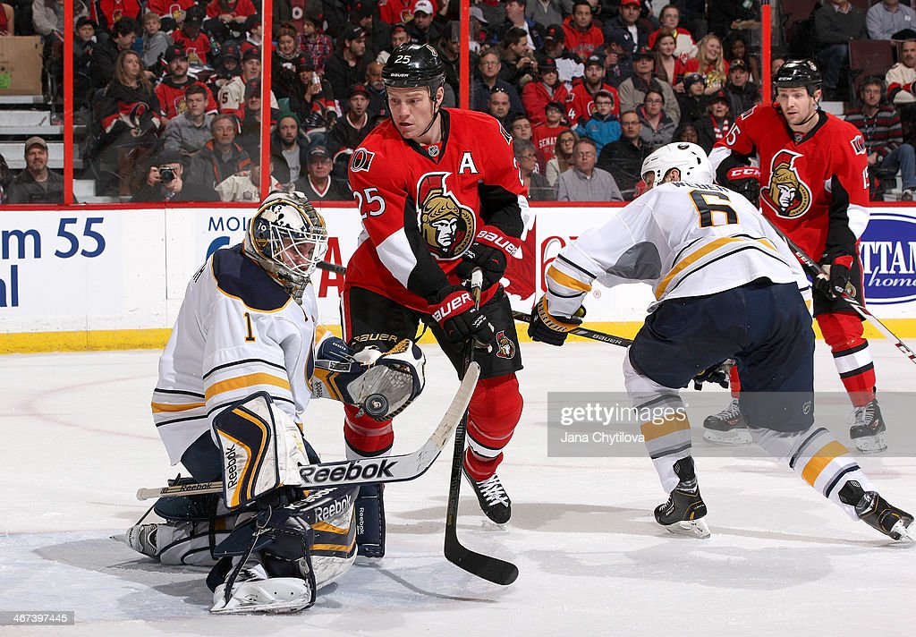 Chris Neil #25 of the Ottawa Senators looks for the rebound as Jhonas Enroth #1 of the Buffalo Sabres deflects the puck and Mike Weber #6 of the Buffalo Sabres and Zack Smith #15 of the Ottawa Senators look on during an NHL game at Canadian Tire Centre on February 6, 2014 in Ottawa, Ontario, Canada.