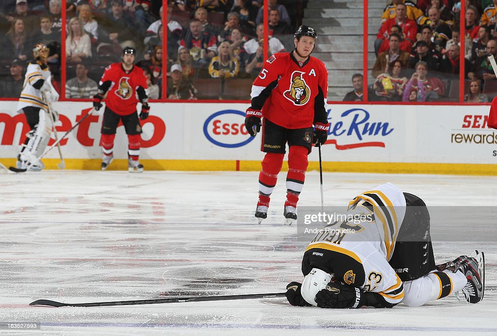 Chris Neil of the Ottawa Senators looks on as Chris Kelly the Boston Bruins crumples to the ice in discomfort after their collision during an NHL...