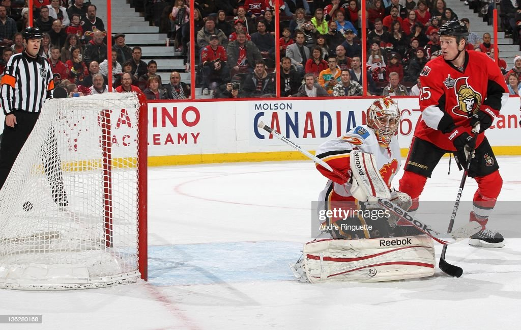 Chris Neil of the Ottawa Senators looks on as the puck hits the back of the net behind Leland Irving of the Calgary Flames for the overtime winner on...