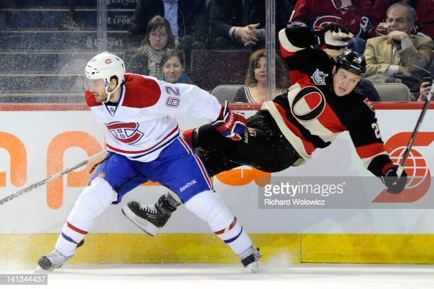 Chris Neil of the Ottawa Senators misses his body check on Frederic StDenis of the Montreal Canadiens during the NHL game at the Bell Centre on March...