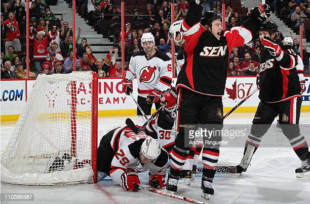 Chris Neil of the Ottawa Senators raises his arms to celebrate what would be his gamewinning goal against Anssi Salmela Martin Brodeur and Andy...