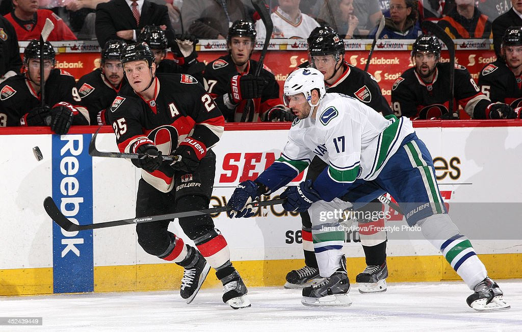 Chris Neil #25 of the Ottawa Senators shoots the puck past the raised stick of <a gi-track='captionPersonalityLinkClicked' href=/galleries/search?phrase=Ryan+Kesler&family=editorial&specificpeople=206915 ng-click='$event.stopPropagation()'>Ryan Kesler</a> #17 of the Vancouver Canucks during an NHL game at Canadian Tire Centre on November 28, 2013 in Ottawa, Ontario, Canada.