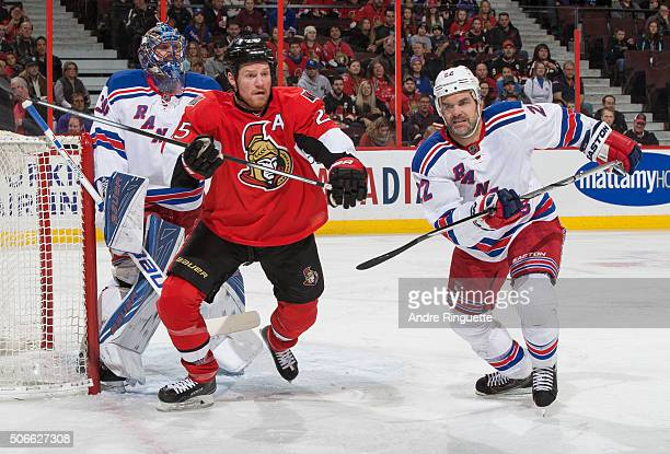 Chris Neil of the Ottawa Senators skates for position outside the crease against Dan Boyle and Henrik Lundqvist of the New York Rangers at Canadian...