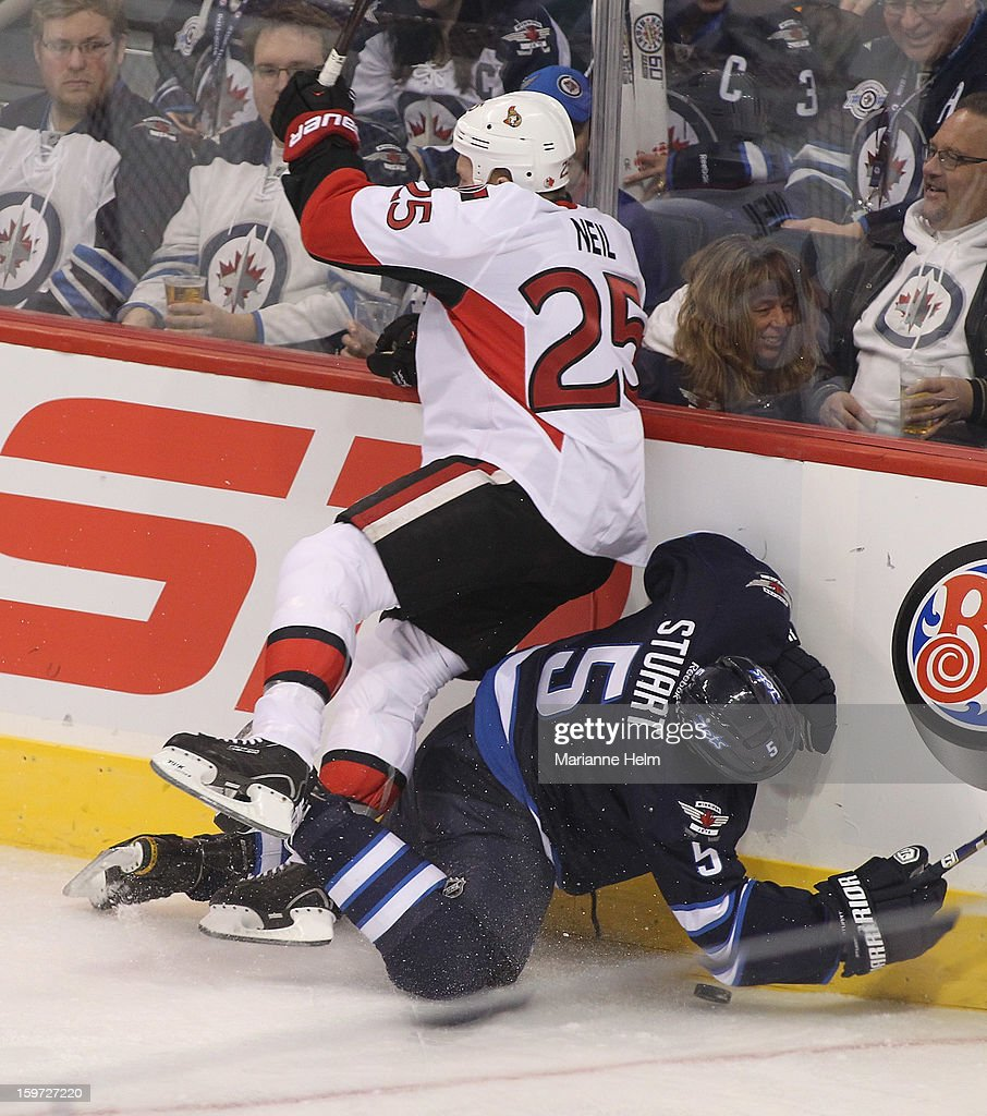 Chris Neil #25 of the Ottawa Senators smashes Mark Stuart #5 of the Winnipeg Jets into the boards during first period action on January 19, 2013 at the MTS Centre in Winnipeg, Manitoba, Canada.