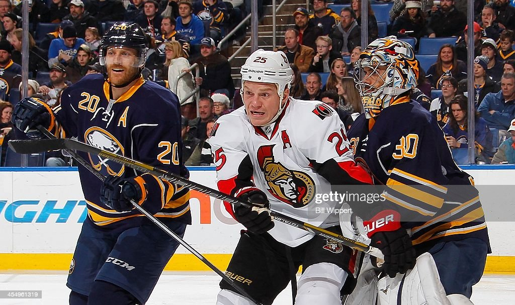 Chris Neil #25 of the Ottawa Senators squeezes between Henrik Tallinder #20 and Ryan Miller #30 of the Buffalo Sabres during the second period on December 10, 2013 at the First Niagara Center in Buffalo, New York.