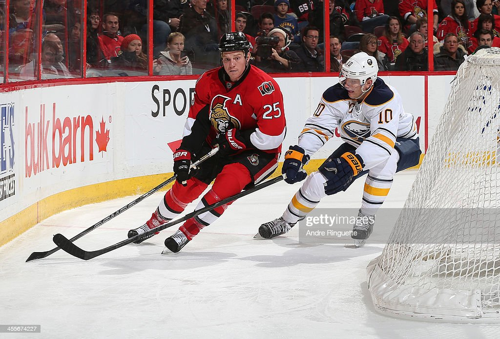 Chris Neil #25 of the Ottawa Senators takes the puck behind the net against <a gi-track='captionPersonalityLinkClicked' href=/galleries/search?phrase=Christian+Ehrhoff&family=editorial&specificpeople=214788 ng-click='$event.stopPropagation()'>Christian Ehrhoff</a> #10 of the Buffalo Sabres at Canadian Tire Centre on December 12, 2013 in Ottawa, Ontario, Canada.