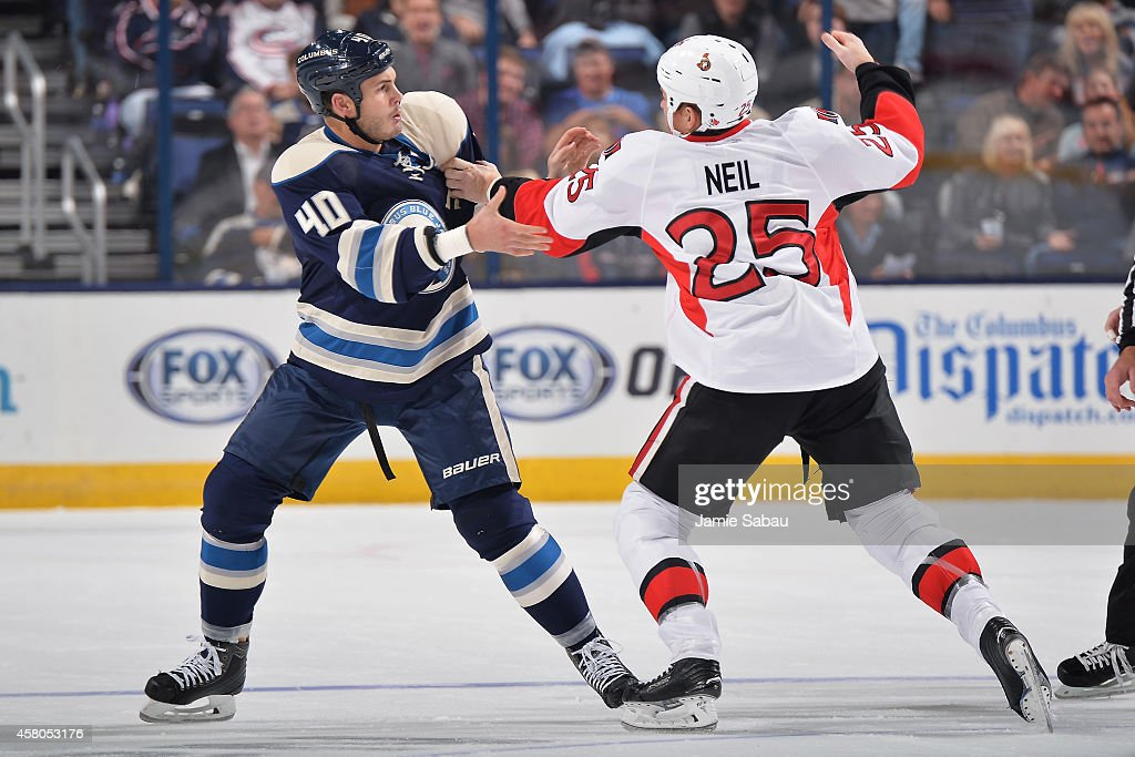 Chris Neil of the Ottawa Senators throws a punch while fighting with Jared Boll of the Columbus Blue Jackets during the first period on October 28...