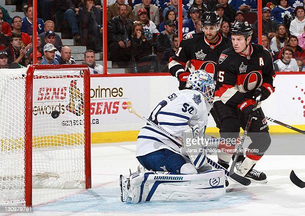 Chris Neil of the Ottawa Senators tips the puck get past Jonas Gustavsson of the Toronto Maple Leafs during an NHL game at Scotiabank Place on...