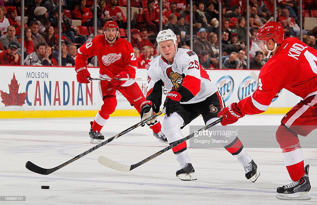 Chris Neil #25 of the Ottawa Senators tries to get around the stick of Jakub Kindl #4 of the Detroit Red Wings during the third period at Joe Louis Arena on October 23, 2013 in Detroit, Michigan. Ottawa won the game 6-1.