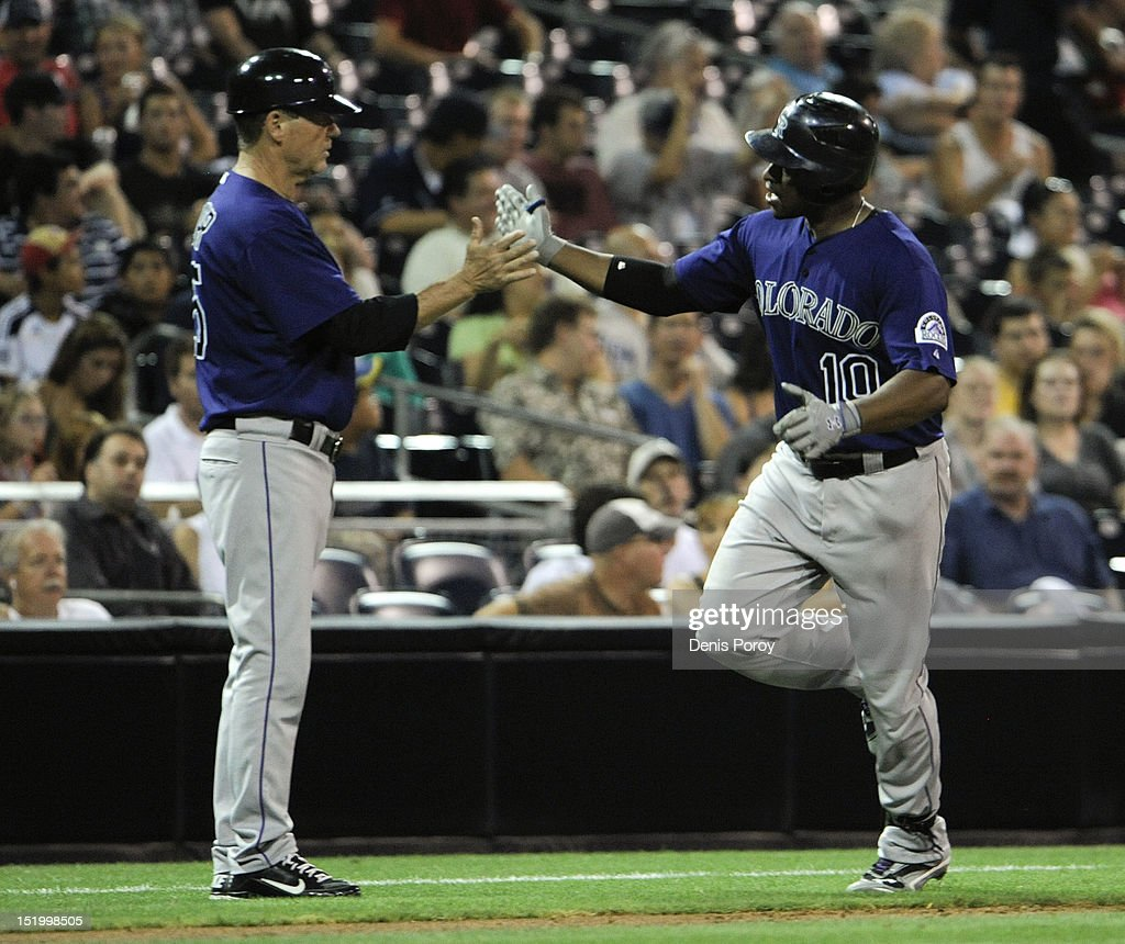 Chris Nelson #10 of the Colorado Rockies, right, is congratulated by Rich Dauer #25 after hitting a solo home run during the third inning of a baseball game against the San Diego Padres at Petco Park on September 14, 2012 in San Diego, California.