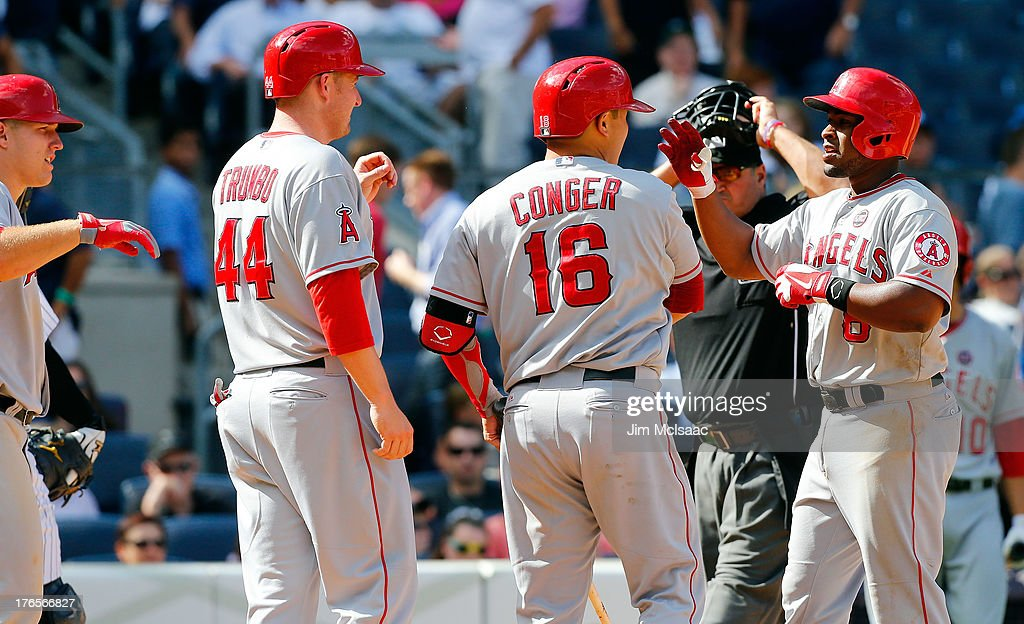 Chris Nelson #8 of the Los Angeles Angels of Anaheim celebrates his eighth inning grand slam against the New York Yankees with teammates <a gi-track='captionPersonalityLinkClicked' href=/galleries/search?phrase=Mike+Trout&family=editorial&specificpeople=7091306 ng-click='$event.stopPropagation()'>Mike Trout</a> #27, <a gi-track='captionPersonalityLinkClicked' href=/galleries/search?phrase=Mark+Trumbo&family=editorial&specificpeople=4921667 ng-click='$event.stopPropagation()'>Mark Trumbo</a> #44 and <a gi-track='captionPersonalityLinkClicked' href=/galleries/search?phrase=Hank+Conger&family=editorial&specificpeople=713039 ng-click='$event.stopPropagation()'>Hank Conger</a> #16 at Yankee Stadium on August 15, 2013 in the Bronx borough of New York City.
