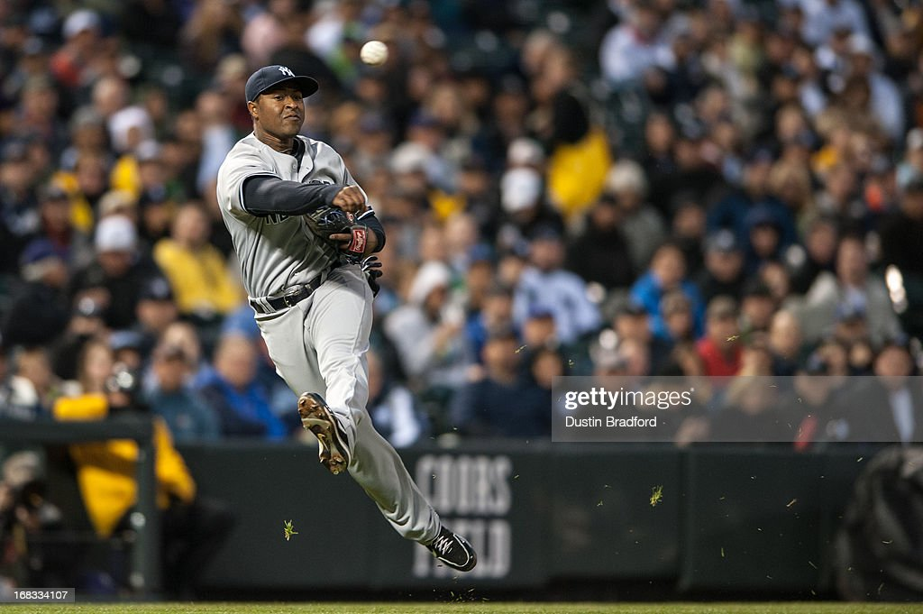 Chris Nelson #39 of the New York Yankees makes an acrobatic throw from third base to put out a runner at first base in the fourth inning of a game against the Colorado Rockies at Coors Field on May 8, 2013 in Denver, Colorado.