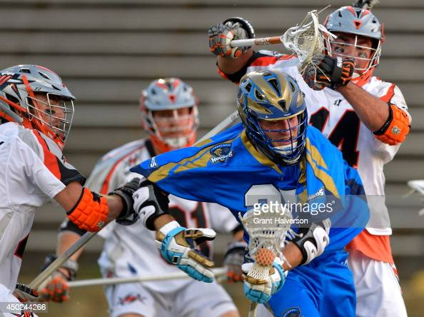 Chris O'Dougherty and Justin Pennington of the Denver Outlaws pressure Ryan Young of the Charlotte Hounds at American Legion Memorial Stadium on June...