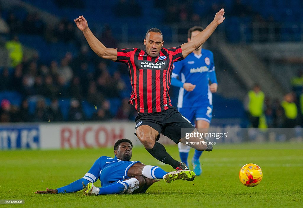 Chris O'Grady of Brighton and Hove Albion is tackled by <a gi-track='captionPersonalityLinkClicked' href=/galleries/search?phrase=Bruno+Ecuele+Manga&family=editorial&specificpeople=7115761 ng-click='$event.stopPropagation()'>Bruno Ecuele Manga</a> of Cardiff City during the Sky Bet Championship match between Cardiff City and Brighton & Hove Albion at Cardiff City Stadium on February 10, 2015 in Cardiff, Wales.