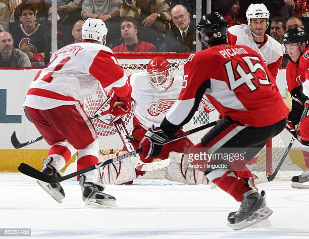 Chris Osgood of the Detroit Red Wings makes a stick save through traffic on a shot by Alexandre Picard of the Ottawa Senators at Scotiabank Place on...