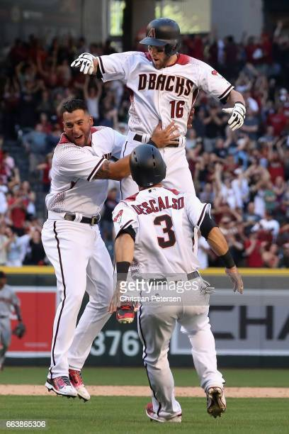 Chris Owings of the Arizona Diamondbacks celebrates with David Peralta and Daniel Descalso after Owings hit the game winning RBI single against the...