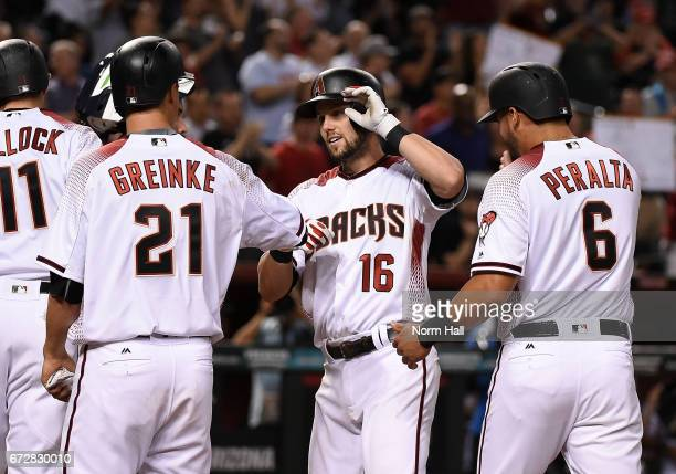 Chris Owings of the Arizona Diamondbacks celebrates with teammates Zack Greinke and David Peralta after hitting a grand slam home run off of Jhoulys...