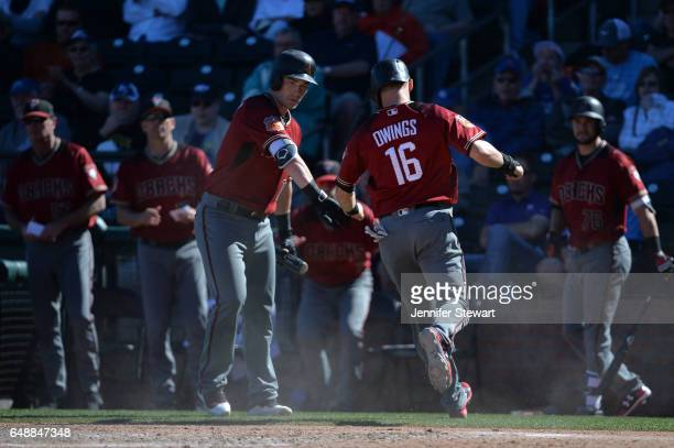 Chris Owings of the Arizona Diamondbacks is congratulated by Chris Herrmann after scoring in the sixth ining against the Kansas City Royals in the...