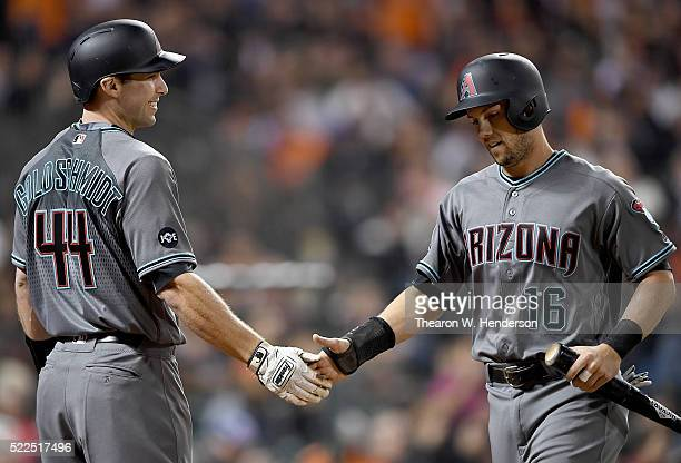 Chris Owings of the Arizona Diamondbacks is congratulated by Paul Goldschmidt after Owings scored against the San Francisco Giants in the top of the...