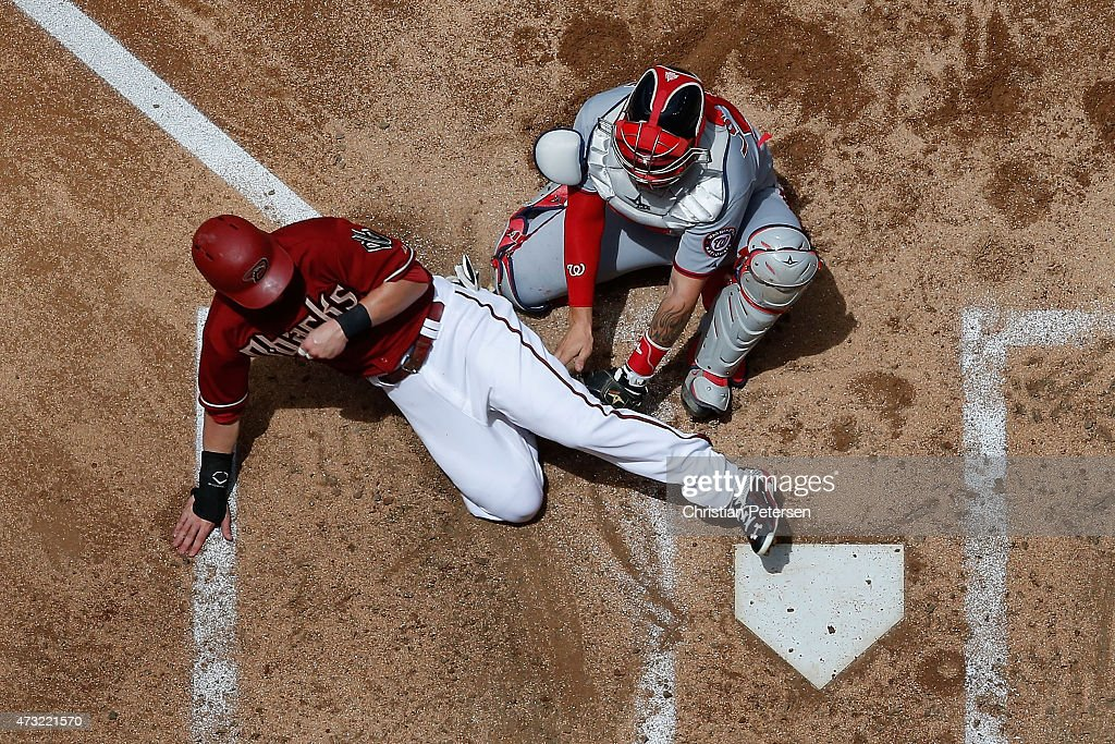 Chris Owings of the Arizona Diamondbacks safely slides in to score a run past catcher Jose Lobaton of the Washington Nationals during the second...
