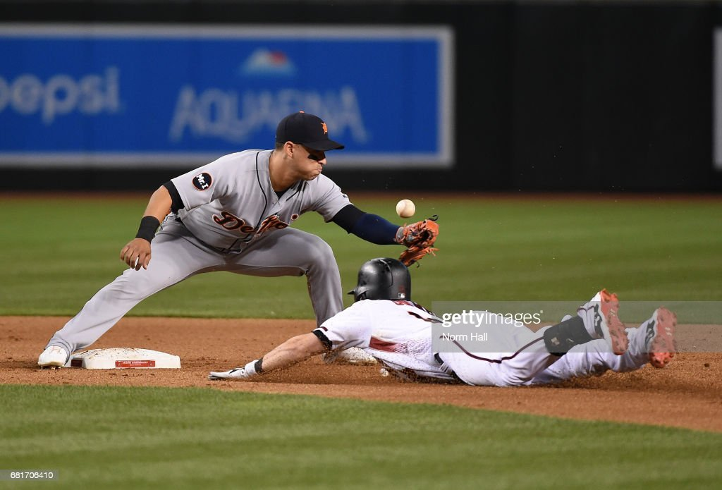 Chris Owings #16 of the Arizona Diamondbacks slides safely into second base as Jose Iglesias #1 of the Detroit Tigers cannot come up with the throw in from the outfield field during the fifth inning at Chase Field on May 10, 2017 in Phoenix, Arizona.