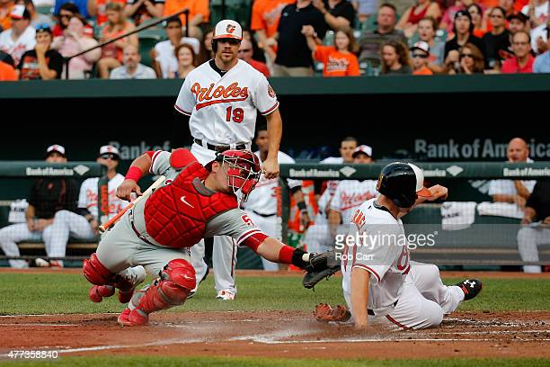 Chris Parmelee of the Baltimore Orioles scores in front of the tag of catcher Carlos Ruiz of the Philadelphia Phillies during the first inning at...