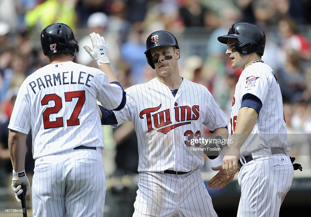 Chris Parmelee #27 of the Minnesota Twins congratulates teammates Justin Morneau #33 and Josh Willingham #16 on scoring against the Texas Rangers on a home run by Morneau during the sixth inning of the game on April 28, 2013 at Target Field in Minneapolis, Minnesota. The Twins defeated the Ranger 5-0.