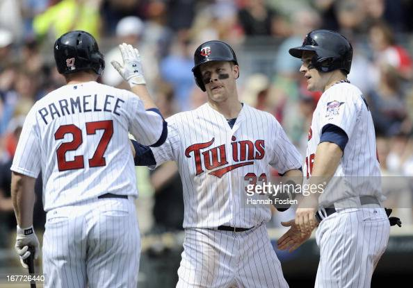 Chris Parmelee of the Minnesota Twins congratulates teammates Justin Morneau and Josh Willingham on scoring against the Texas Rangers on a home run...