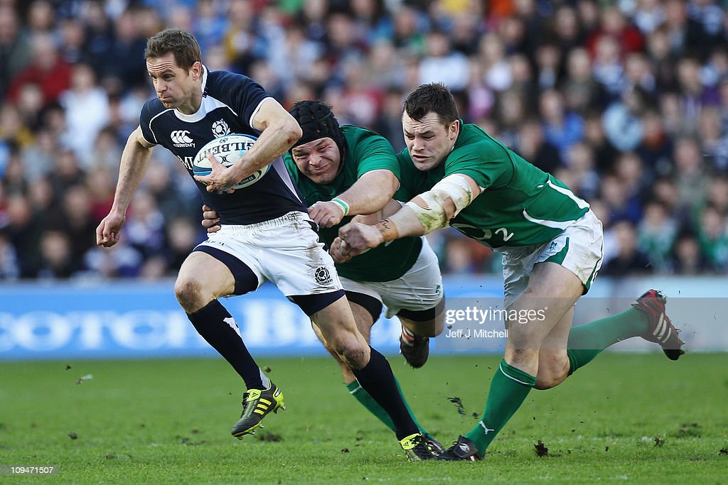 Chris Paterson of Scotland escapes the challenge of Mike Ross and Cian Healy of Ireland during the RBS 6 Nations Championship match between Scotland...