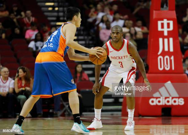 Chris Paul of Houston Rockets defends Shi Yuchen of Shanghai Sharks in the first half at Toyota Center on October 5 2017 in Houston Texas NOTE TO...