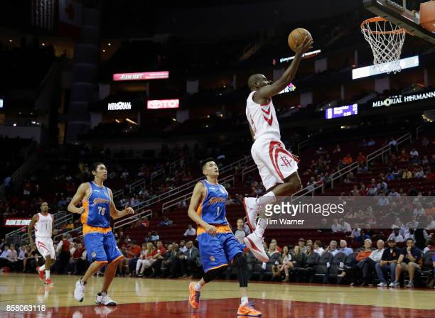 Chris Paul of Houston Rockets goes up for a layup on a fast break defended by Cai Liang of Shanghai Sharks and Tseng Wenting in the first half at...