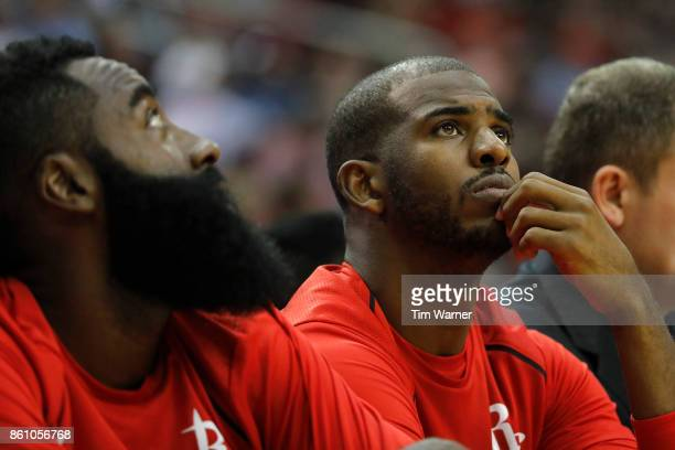 Chris Paul of the Houston Rockets watches from the bench in the first half against the San Antonio Spurs at Toyota Center on October 13 2017 in...