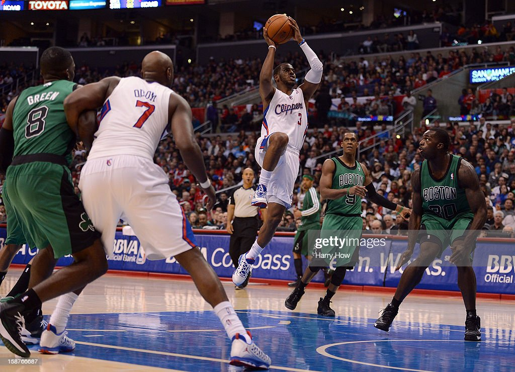 Chris Paul #3 of the Los Angeles Clippers attempts a layup in front of Brandon Bass #30 and Rajon Rondo #9 of the Boston Celtics during a 106-77 Clipper win for 15 straight wins at Staples Center on December 27, 2012 in Los Angeles, California.