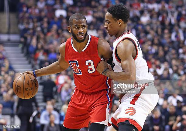Chris Paul of the Los Angeles Clippers drives against DeMar DeRozan of the Toronto Raptors during an NBA game at the Air Canada Centre on January 24...