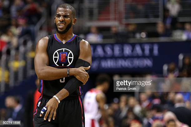 Chris Paul of the Los Angeles Clippers holds his left arm against the Washington Wizards during the first half at Verizon Center on December 28 2015...